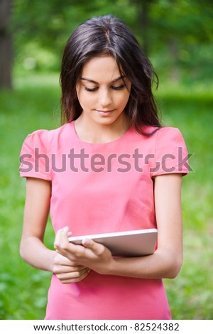Young charming dark-haired woman works on tablet computer in green summer city park.,