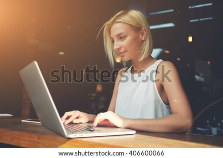 Young charming female freelancer using laptop computer for distance job while sitting in modern coffee shop interior, beautiful Caucasian woman working on net-book during morning breakfast in cafe bar