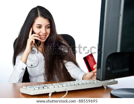 young charming girl sitting at the computer and talking on the phone with a business card in his hand,isolated over white