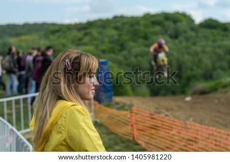 Young charming girl spectator fan at motocross competitions
