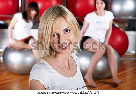 Young charming girls go in for sports in sport hall