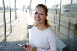 Young charming hipster girl with cute smile holding smart phone and smile to the camera while waiting a bus on station, happy smiling woman in urban setting using cell telephone for chat with friend