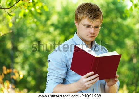 young, charming, serious student (male) with glasses reading book on background of summer park