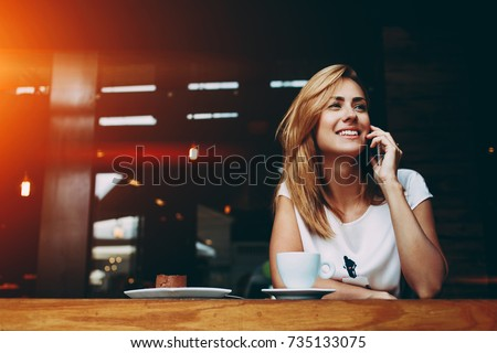 Young charming woman calling with cell telephone while sitting alone in coffee shop during free time, attractive female with cute smile having talking conversation with mobile phone while rest in cafe #735133075