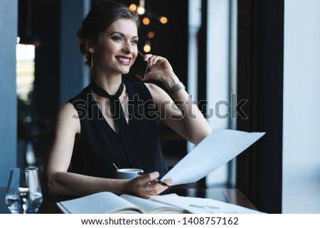 Young charming woman calling with cell telephone while sitting in coffee shop during free time, attractive female having talking conversation with mobile phone while rest in cafe