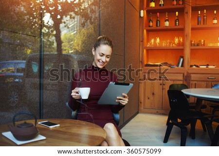 Young charming woman have video ����hat with sister via digital tablet while sitting in her favorite cafe drinking delicious green tea, female watching movie on touch pad while breakfast in coffee shop