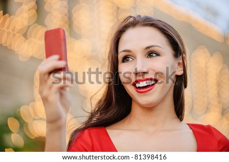 Young charming woman in red dress reads text message on mobile phone and laughs.
