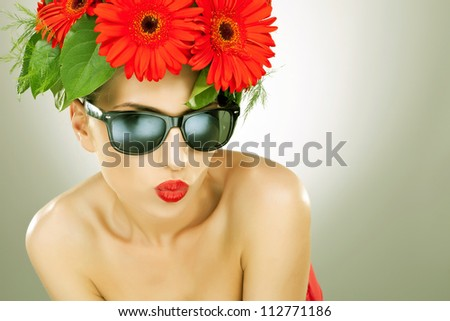 young charming woman with flowers in her hair and wearing sunglasses sending you a kiss- vintage picture style