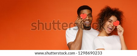 Young cheerful african-american couple in love holding red hearts over eyes and smiling, orange panorama background with empty space