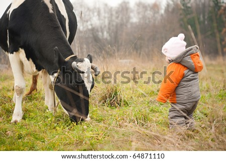 young cheerful baby stay near feeding cow