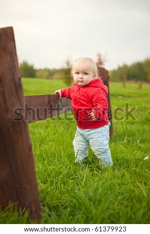young cheerful baby walk by grass along wood fence in park