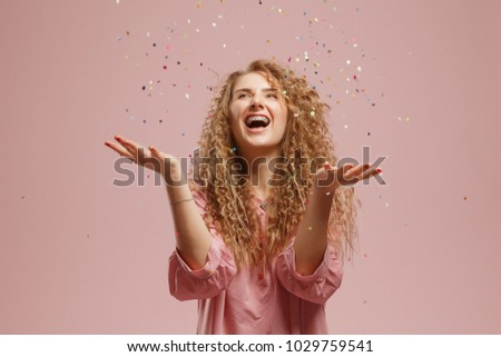 Young cheerful beautiful blonde girl in pink dress smiling with handful of confetti over background. Concept party, holiday, surprise