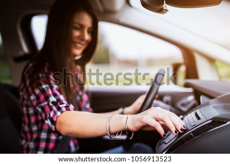 Young cheerful beautiful girl is adjusting a volume of her stereo in the car she is driving.