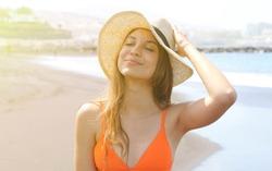 Young cheerful bikini woman with hat enjoying sun on tropical beach. Relaxing sunbathing holidays in Tenerife.