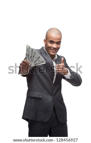 young cheerful black businessman holding money and showing thumb up isolated on white