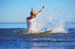 Young cheerful blonde girl enjoys swimming in the sea. She splashing in water and transparent spray scatter in different directions, creating a beautiful background.