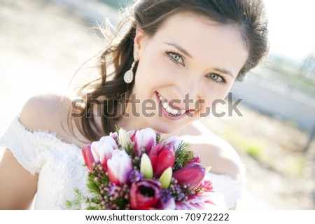 Young cheerful bride holding her bouquet