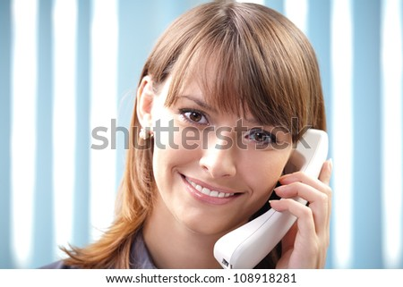 Young cheerful business woman with phone at office