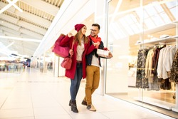 Young cheerful caucasian couple walking by the shop window embraced, doing Christmas shopping in a shopping mall. They are carrying shopping bags and gift.