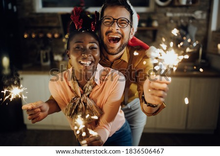 Young cheerful couple having fun with sparklers on New Year's eve at home.