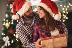 Young cheerful couple in love with gift for Christmas