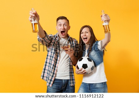 Young cheerful couple supporter, woman man, football fans cheer up support team, holding beer bottle, pizza slice, soccer ball isolated on yellow background. Sport, family leisure, lifestyle concept #1116912122