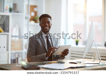Young cheerful economist or analyst in formalwear scrolling in touchpad while surfing for necessary data in the net
