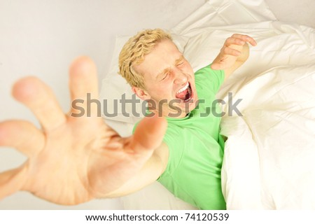 Young cheerful european man in his bed stretching for waking up. Volume perspective shot.