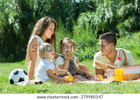 Young cheerful family with little daughters having holiday with picnic at park in summer day