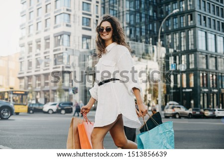 Young cheerful fashionable woman posing on camera during walking on street. Shopaholic with bags in big city. Look back and smile. Urban view and modern buildings behind ストックフォト ©