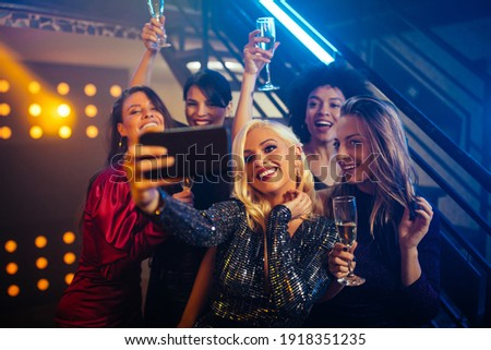 Young cheerful females taking a selfie together in a nightclub Stockfoto ©