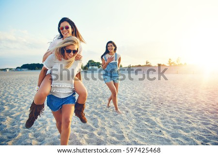 Young cheerful girl giving her friend piggyback ride while third girl laughing at them.  #597425468