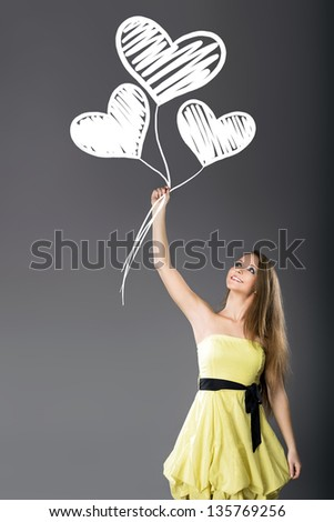 Young cheerful girl hold hand-drawn white hearts balloons
