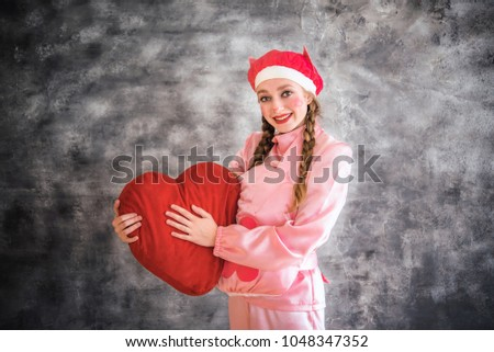 Young cheerful girl in a bright pink suit with a big red heart in hands on a gray background. Animator, costume show, carnival. Bright picture for a poster, bright cheerful card. Carnival costume pig. #1048347352