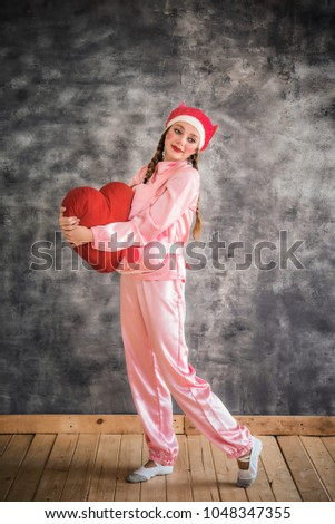 Young cheerful girl in a bright pink suit with a big red heart in hands on a gray background. Animator, costume show, carnival. Bright picture for a poster, bright cheerful card. Carnival costume pig. #1048347355