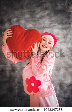 Young cheerful girl in a bright pink suit with a big red heart in hands on a gray background. Animator, costume show, carnival. Bright picture for a poster, bright cheerful card. Carnival costume pig. #1048347358