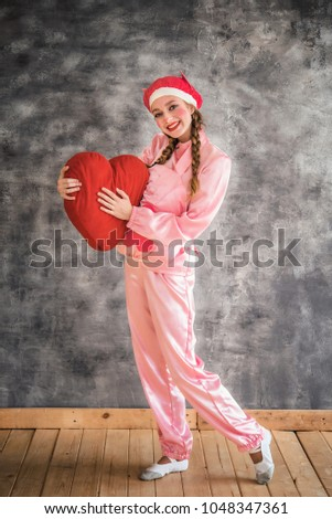 Young cheerful girl in a bright pink suit with a big red heart in hands on a gray background. Animator, costume show, carnival. Bright picture for a poster, bright cheerful card. Carnival costume pig. #1048347361