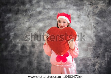 Young cheerful girl in a bright pink suit with a big red heart in hands on a gray background. Animator, costume show, carnival. Bright picture for a poster, bright cheerful card. Carnival costume pig. #1048347364