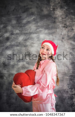 Young cheerful girl in a bright pink suit with a big red heart in hands on a gray background. Animator, costume show, carnival. Bright picture for a poster, bright cheerful card. Carnival costume pig. #1048347367