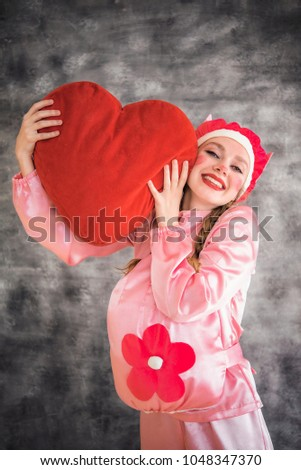 Young cheerful girl in a bright pink suit with a big red heart in hands on a gray background. Animator, costume show, carnival. Bright picture for a poster, bright cheerful card. Carnival costume pig. #1048347370