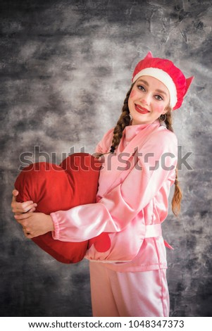 Young cheerful girl in a bright pink suit with a big red heart in hands on a gray background. Animator, costume show, carnival. Bright picture for a poster, bright cheerful card. Carnival costume pig. #1048347373