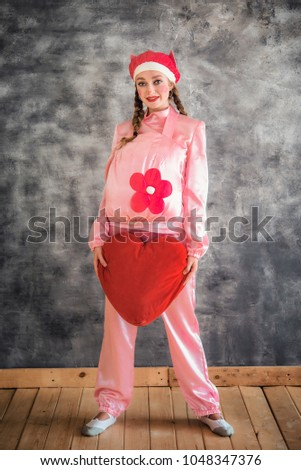 Young cheerful girl in a bright pink suit with a big red heart in hands on a gray background. Animator, costume show, carnival. Bright picture for a poster, bright cheerful card. Carnival costume pig. #1048347376