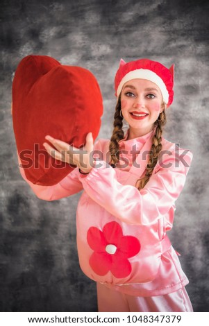 Young cheerful girl in a bright pink suit with a big red heart in hands on a gray background. Animator, costume show, carnival. Bright picture for a poster, bright cheerful card. Carnival costume pig. #1048347379