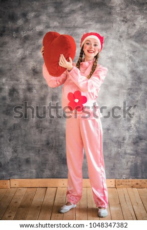 Young cheerful girl in a bright pink suit with a big red heart in hands on a gray background. Animator, costume show, carnival. Bright picture for a poster, bright cheerful card. Carnival costume pig. #1048347382