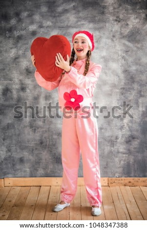 Young cheerful girl in a bright pink suit with a big red heart in hands on a gray background. Animator, costume show, carnival. Bright picture for a poster, bright cheerful card. Carnival costume pig. #1048347388