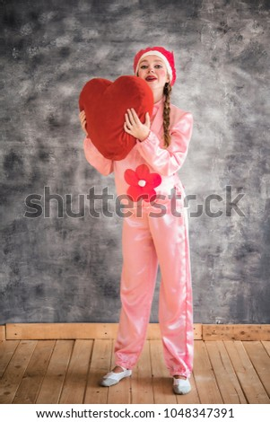 Young cheerful girl in a bright pink suit with a big red heart in hands on a gray background. Animator, costume show, carnival. Bright picture for a poster, bright cheerful card. Carnival costume pig. #1048347391