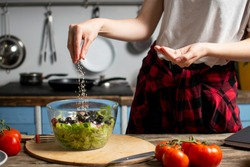 young cheerful girl prepares a vegetarian salad in the kitchen, she salts and adds spices, the process of preparing healthy food