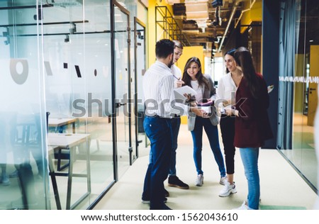 Young cheerful group of coworkers joyfully socializing taking notes and sharing thoughts while discussing ideas and standing in passageway among office spaces. Young coworkers discussing new project #1562043610