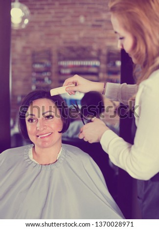 Young  cheerful  hairdresser does to woman haircut with use of scissors and hairbrushes in hairdress salon