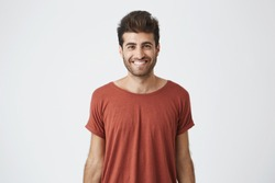 Young cheerful hispanic guy in red t-shirt brightly smiling hearing good news from friend. Beardy handsome student looking at camera with joyful smile